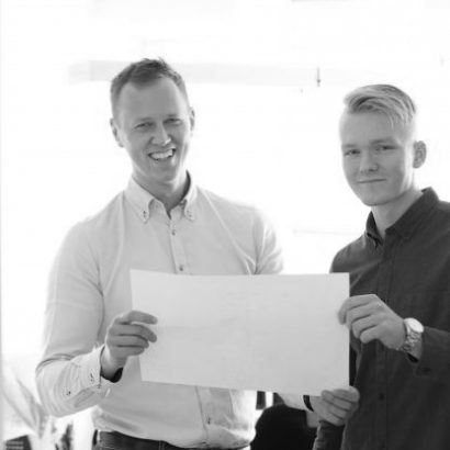 Two smiling young men holding a blueprint together